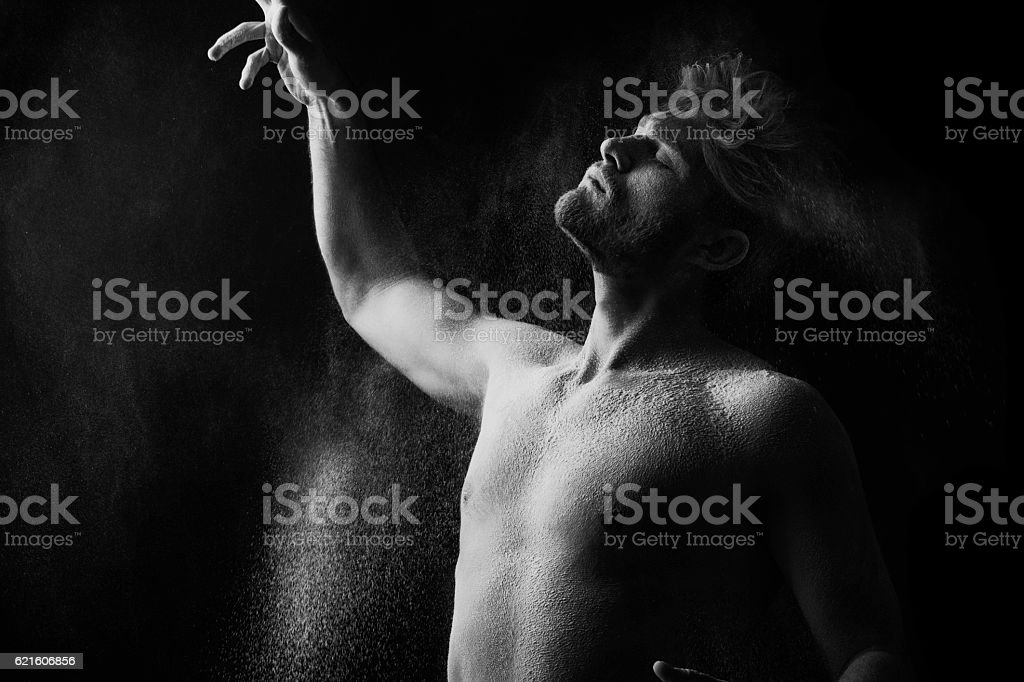 Artistic portrait of man in motion with powder splash royalty-free stock photo