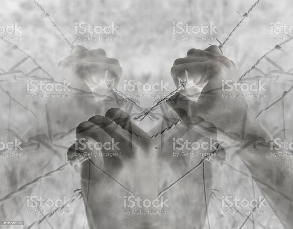 Artistic surreal tortured hands grasping desperately barbed wire (infrared) stock photo