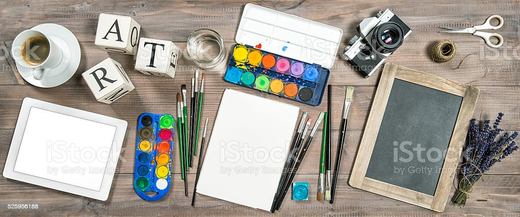 Artistic workplace. Watercolor brushes digital tablet camera stock photo