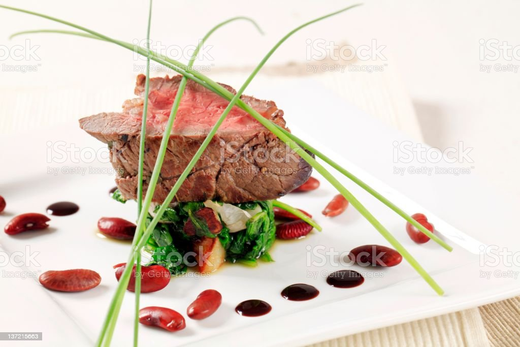 Artistically displayed portion of roast beef and spinach stock photo