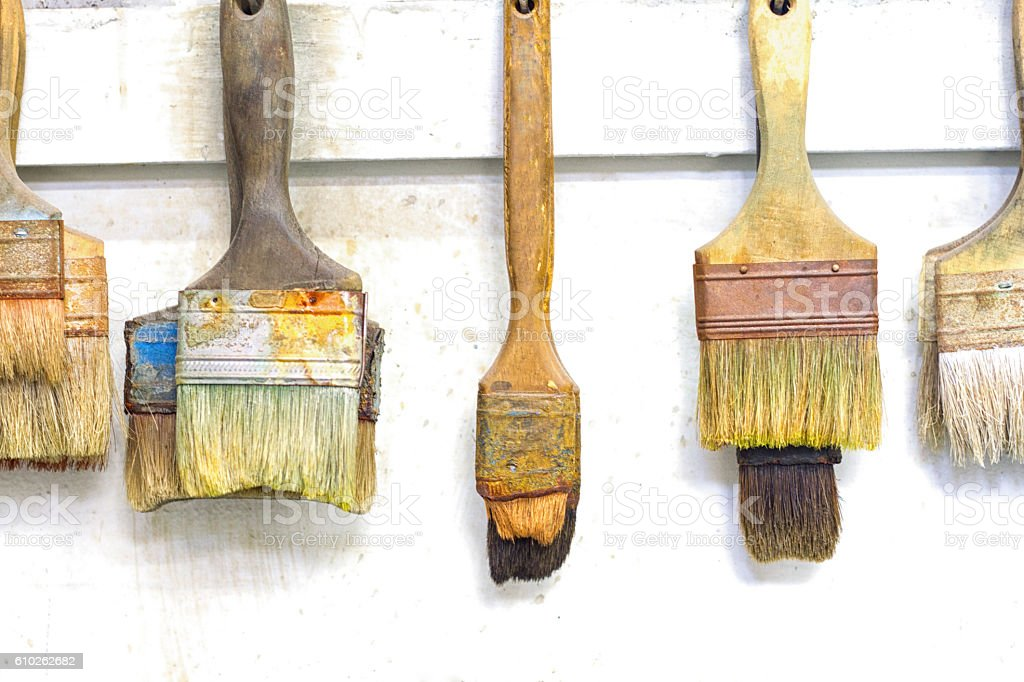Artist's Colorful Paintbrushes Hang on White Wall stock photo