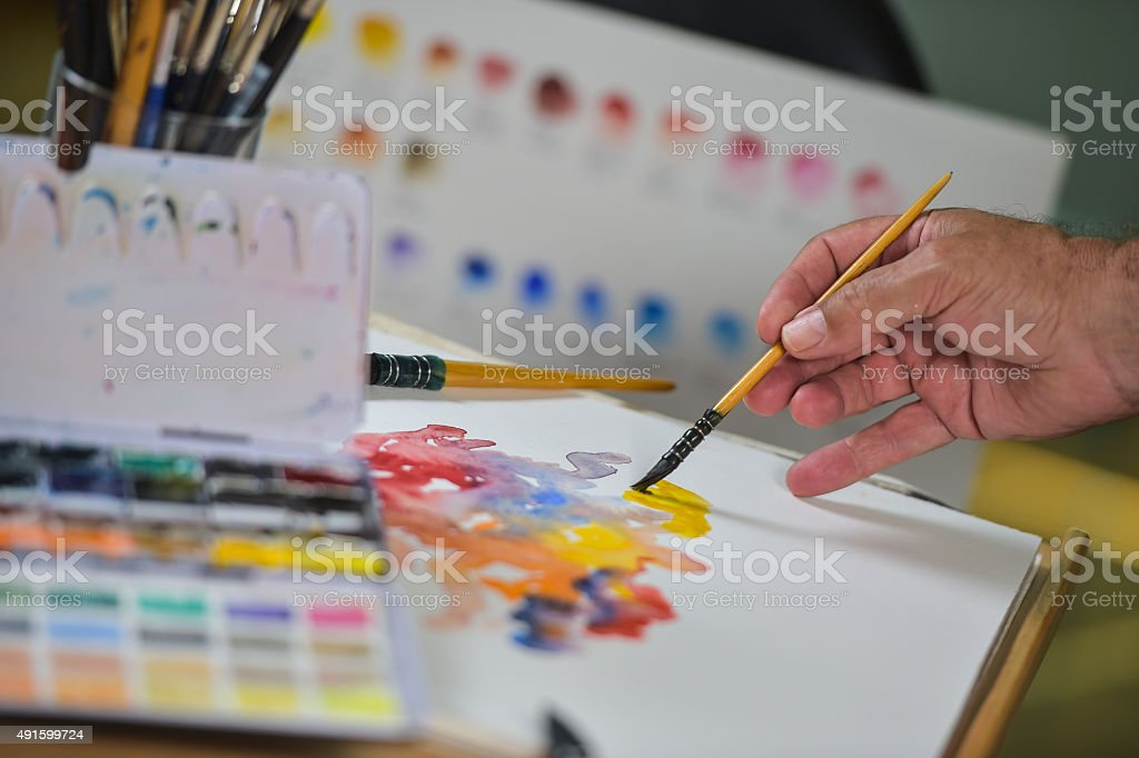 Artist's hand applying paint gouache on the drawing sheet stock photo