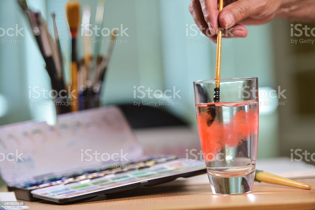 Artist's hand cleaning his brush in a glass of water stock photo