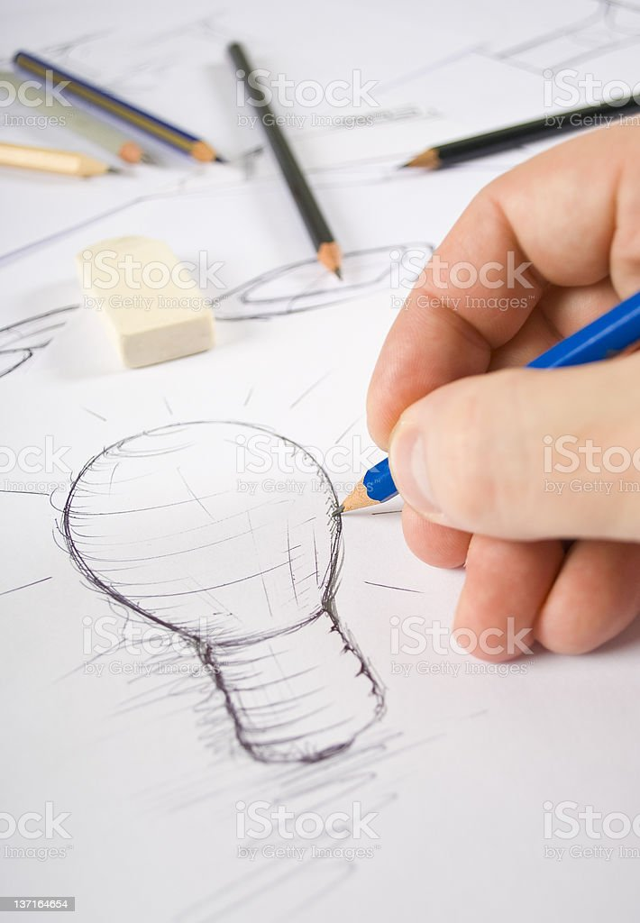 Artist's hands drawing a pencil sketch of a lightbulb stock photo