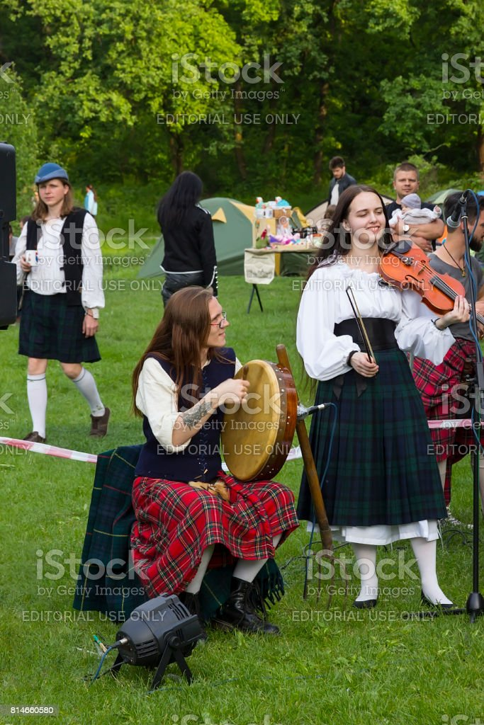 Artists in Scottish national costumes play musical instruments stock photo