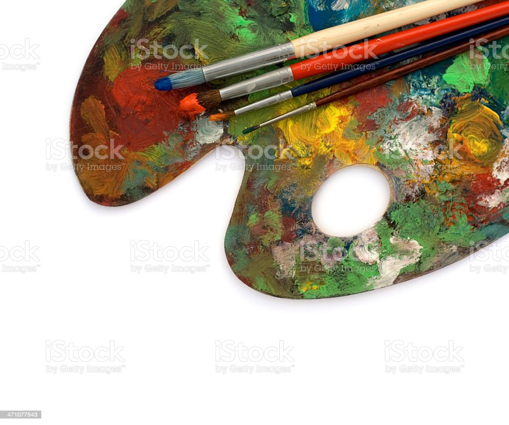 Artist's messy palette with four colored brushes stock photo