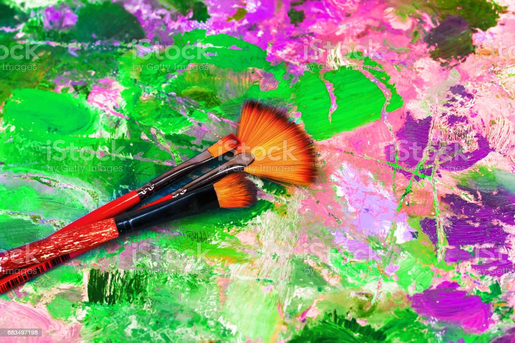 artist's palette with oil paints and brushes for painting stock photo