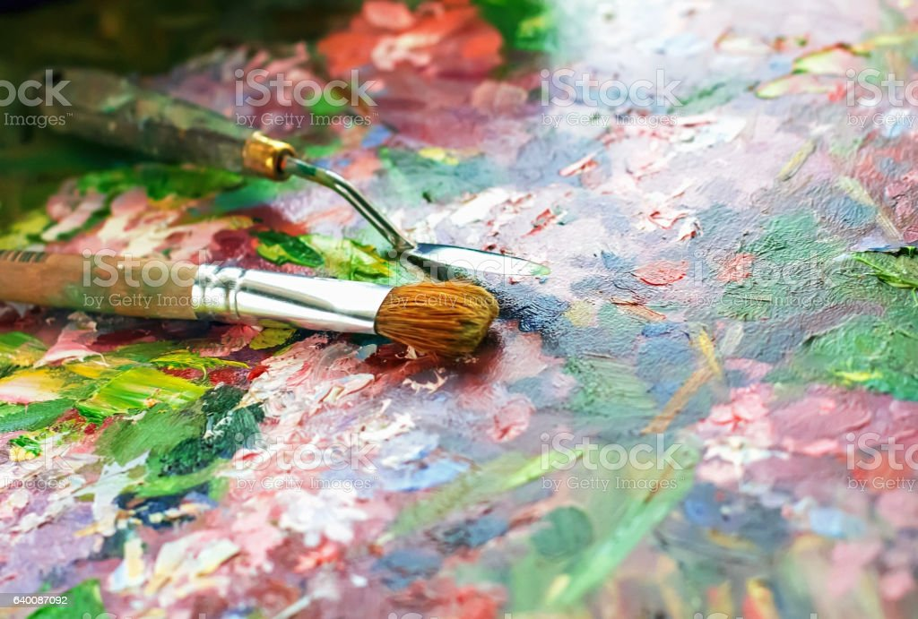 artist's palette with oil paints and brushes stock photo