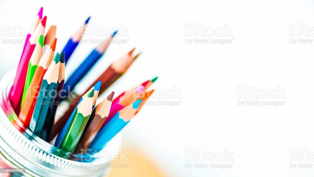 Artist's supplies: Watercolor pencils in glass jar on desk stock photo
