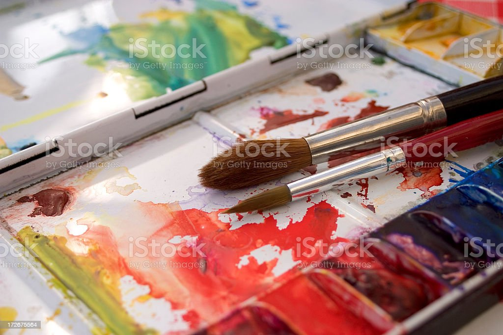 Artists watercolour paint palette and brushes in use close up royalty-free stock photo