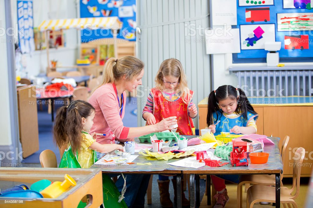 Teacher and nursery students doing arts and crafts in the classroom.