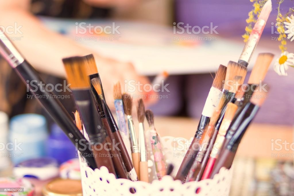 Paintbrush with multiple colored jars. Creative hobby