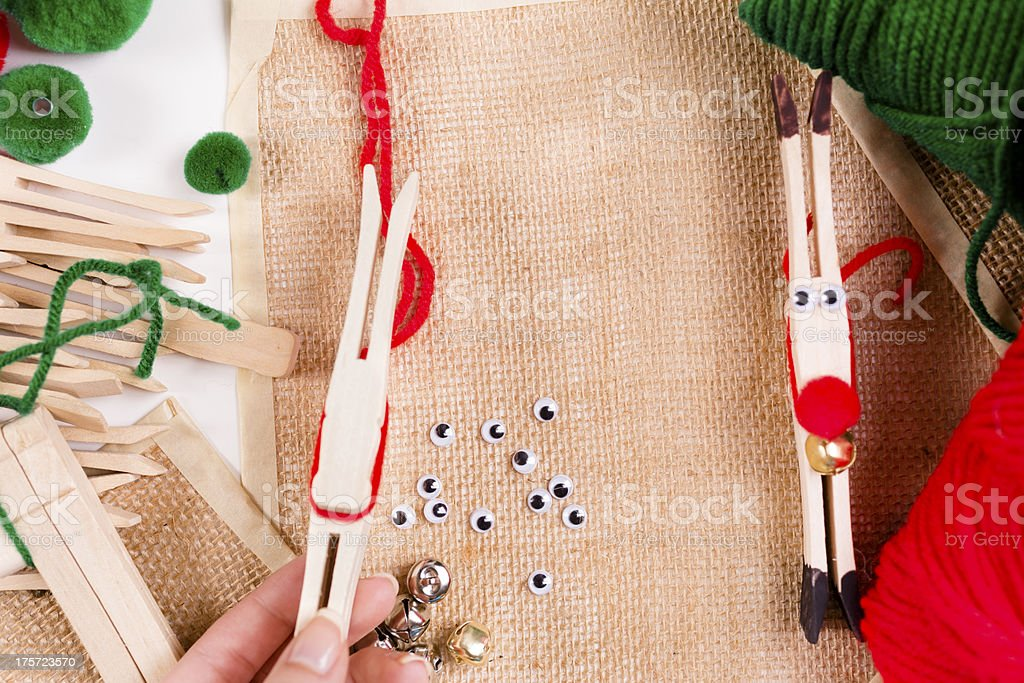Arts and Crafts: Woman making reindeer ornaments with clothespins. royalty-free stock photo