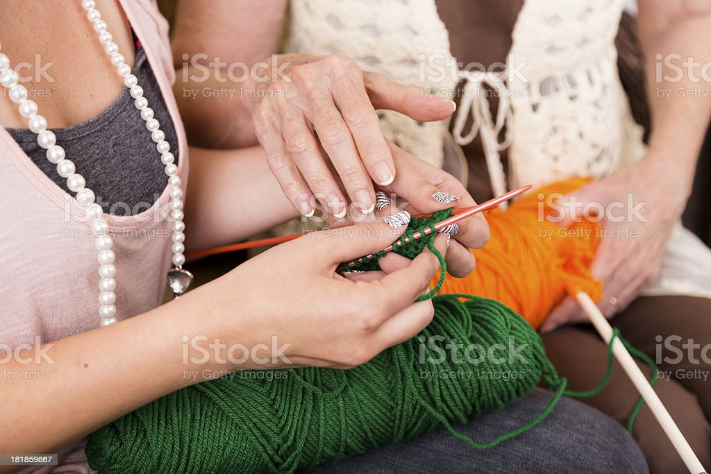Arts Crafts: Senior Woman shows Young Adult how to knit royalty-free stock photo