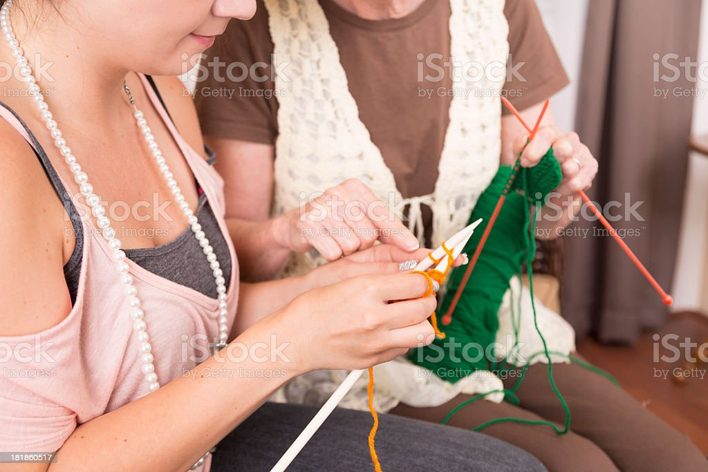 Arts Crafts: Senior Woman teaches Young Adult how to knit royalty-free stock photo