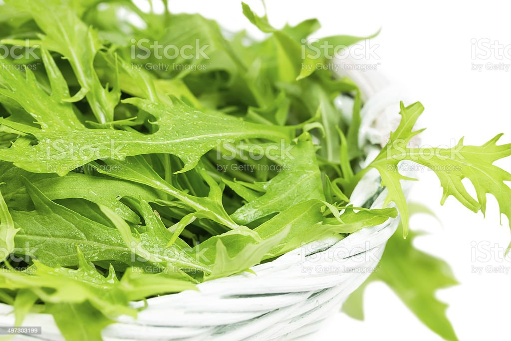Arugula salad in a wicker basket stock photo
