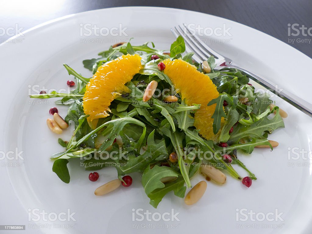 Arugula salad with oranges and pine nuts royalty-free stock photo