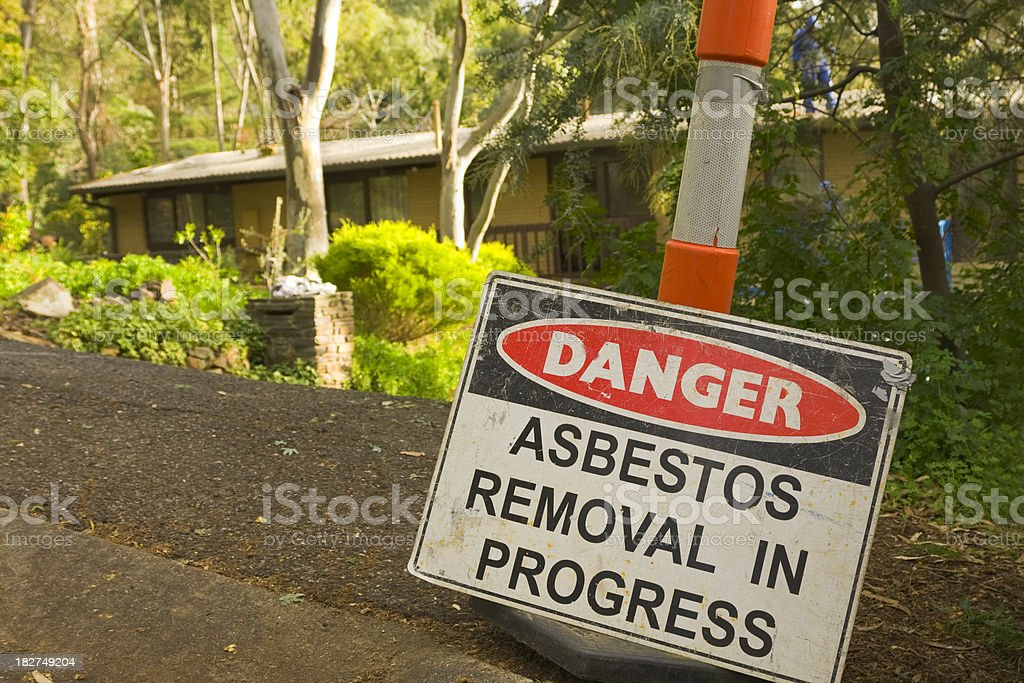 Asbestos removal warning sign in front of a suburban home royalty-free stock photo
