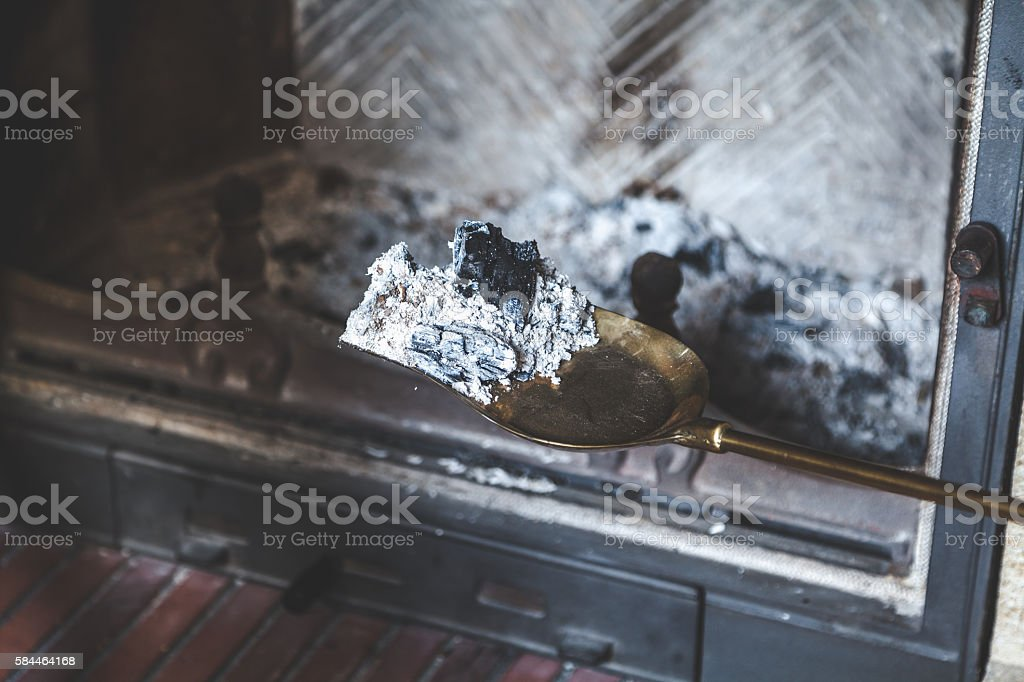 Ash from fire lay extinguished on brass blade stock photo