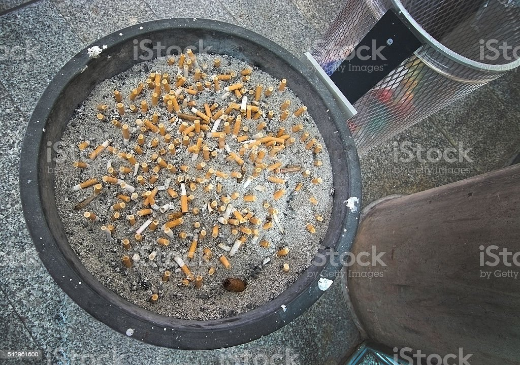 Ashtray full with cigarette stubs stock photo