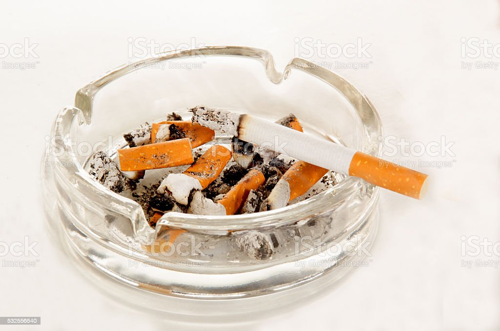 ashtray with cigarette on bright background stock photo