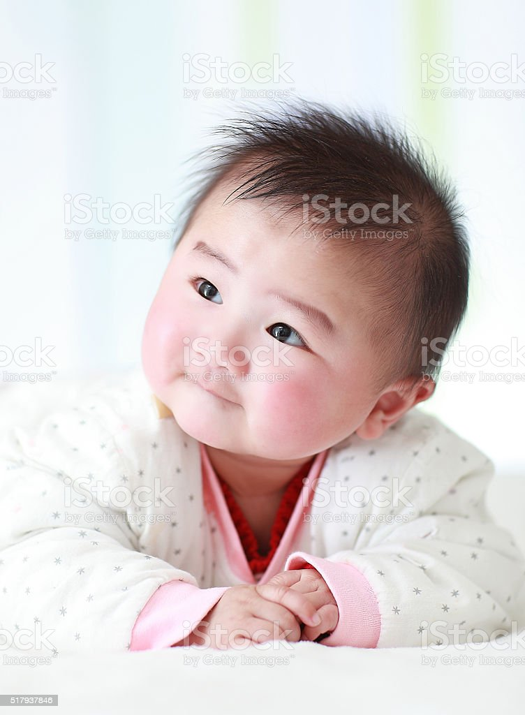 Asia baby is playing on the bed stock photo