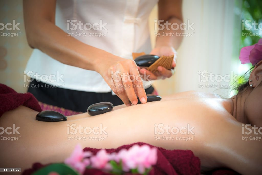 Asia beauty woman lying down on massage bed with traditional hot stones along the spine at Thai spa and wellness center, so relax and lifestyle.  Healthy Concept stock photo