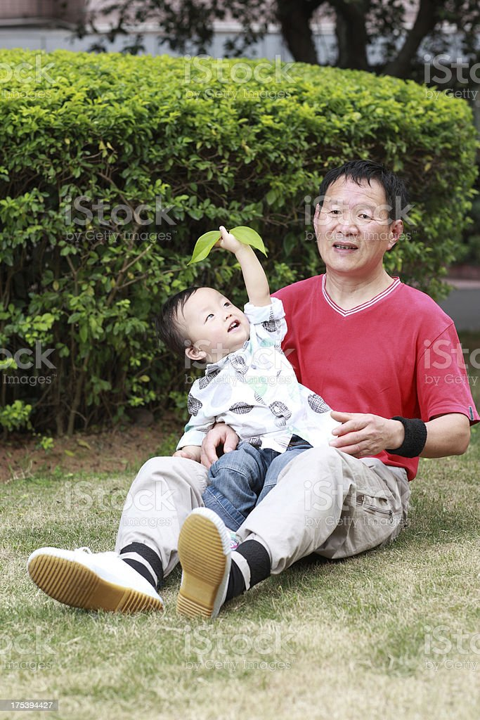 Asia grandfather playing in park with grandson royalty-free stock photo