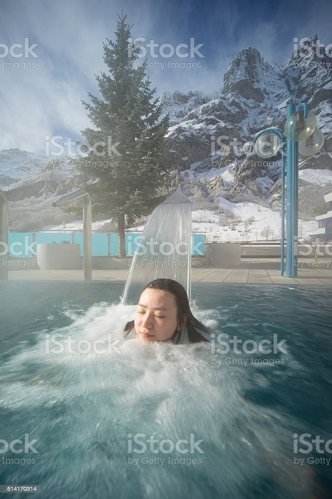 Asia woman enjoy hot spring in Alps stock photo
