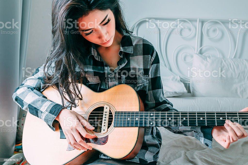 asia women playing guitar stock photo