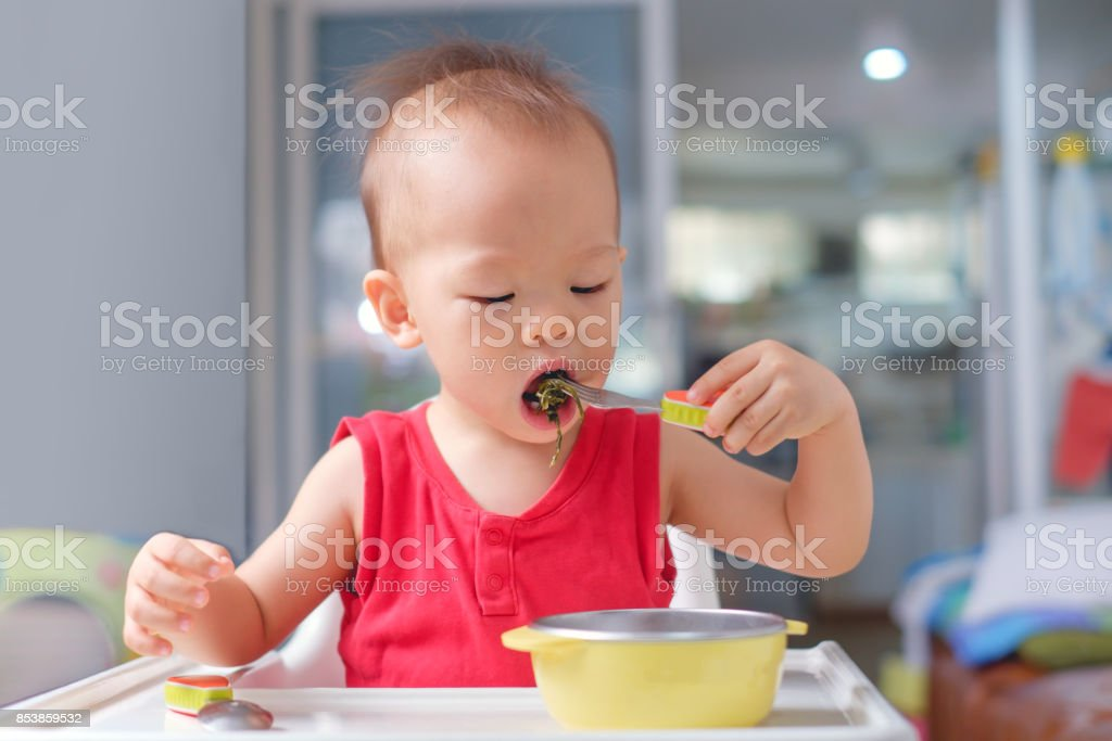 Asian 20 months / 1 year old toddler baby boy child eating healthy food from fork & spoon, stock photo