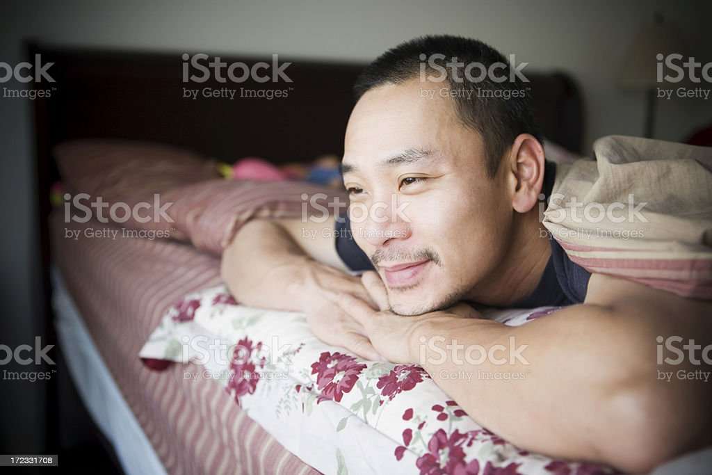 Asian Adult Man Looking Out Home Window from Bedroom, Copyspace stock photo