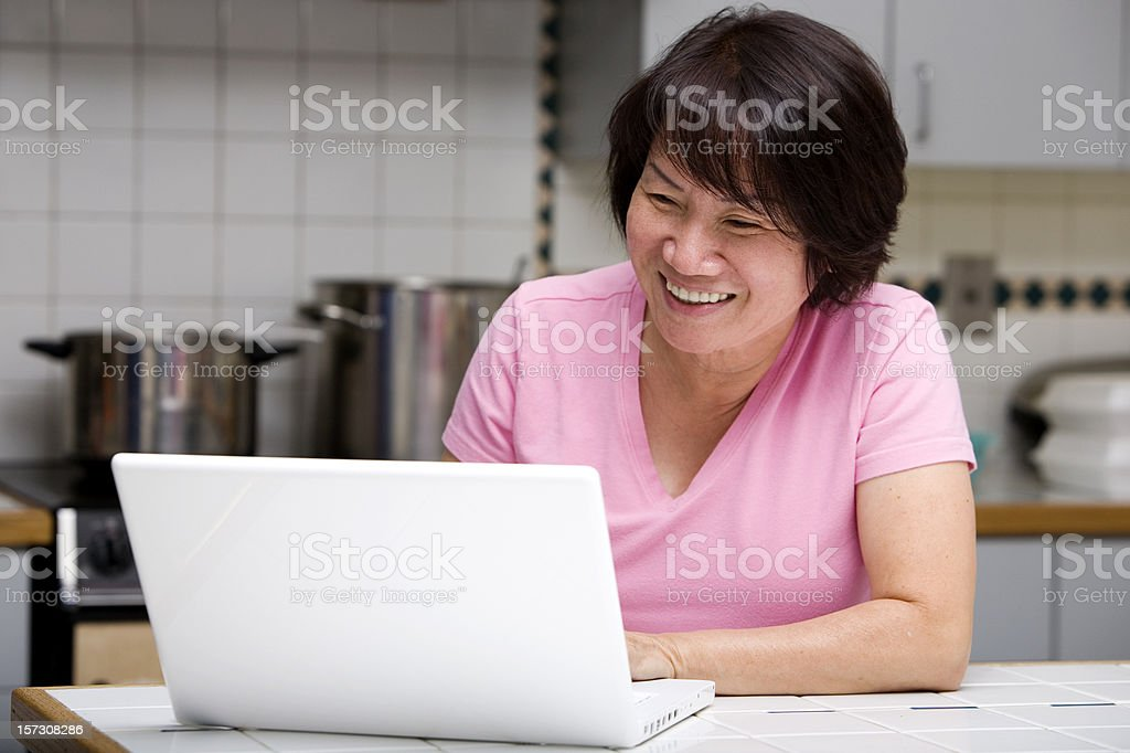Asian Adult Woman Laughing and Smiling, Using Laptop in Kitchen stock photo