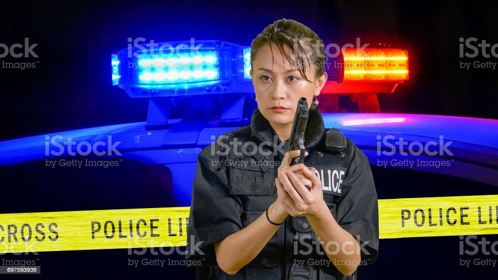 Asian American Policewoman pointing a pistol stock photo