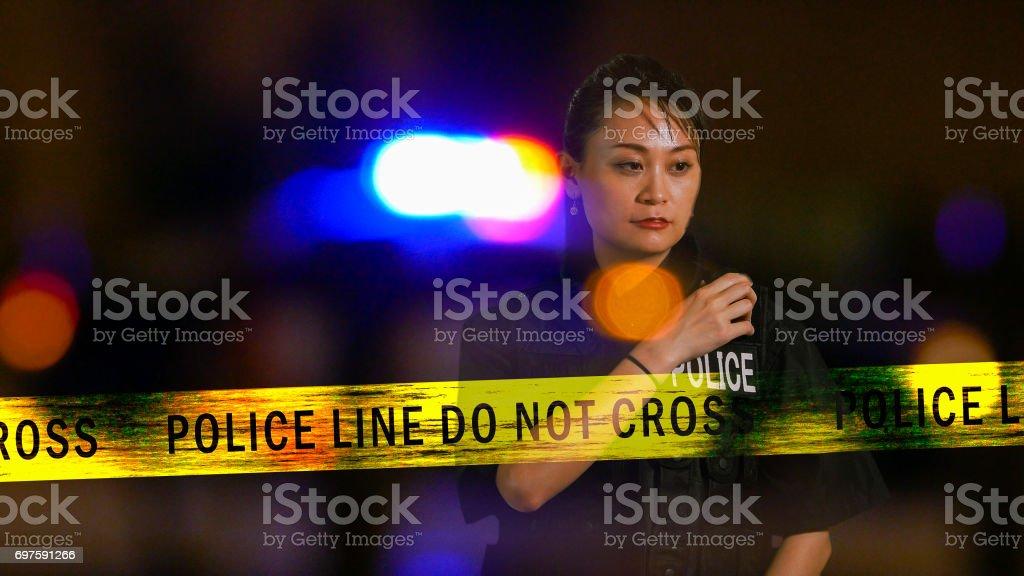 Asian American Policewoman using police radio stock photo