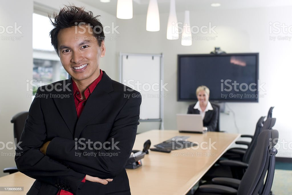 Asian and Caucasian Business Team in Conference Room, Smiling, Copyspace royalty-free stock photo