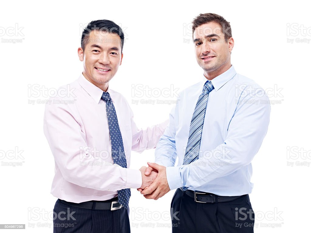 asian and caucasian businessmen shaking hands stock photo