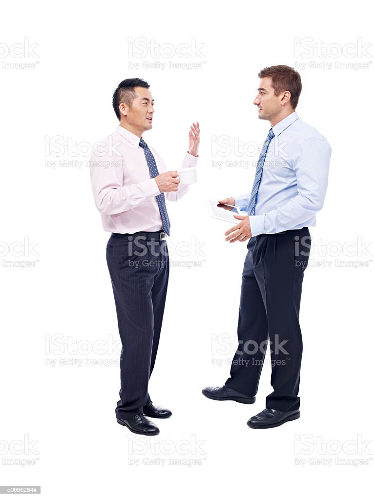 asian and caucasian businessmen talking stock photo