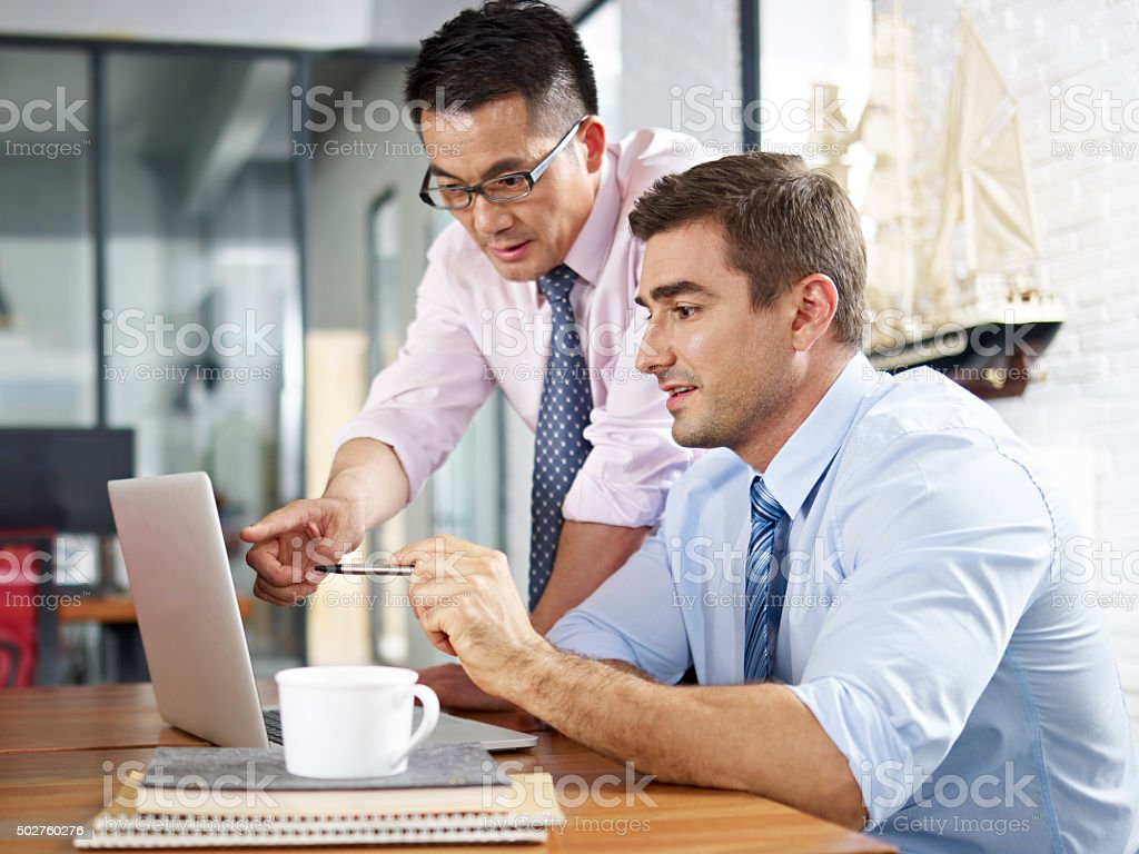 asian and caucasian businessmen working together in office stock photo