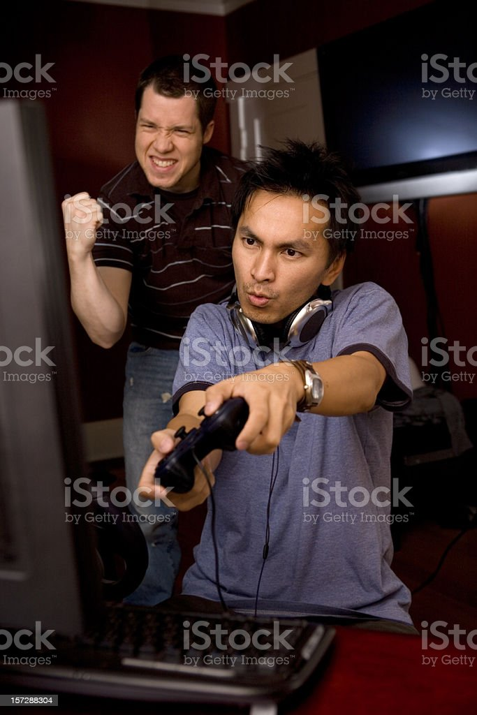 Asian and Caucasian Male Desktop Gamers at Home royalty-free stock photo