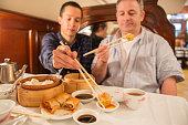 Asian and Caucasian Men Share Dim Sum Lunch in Restaurant