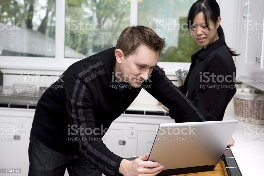 Asian and Caucasian Mixed Young Couple Using Laptop in Kitchen royalty-free stock photo