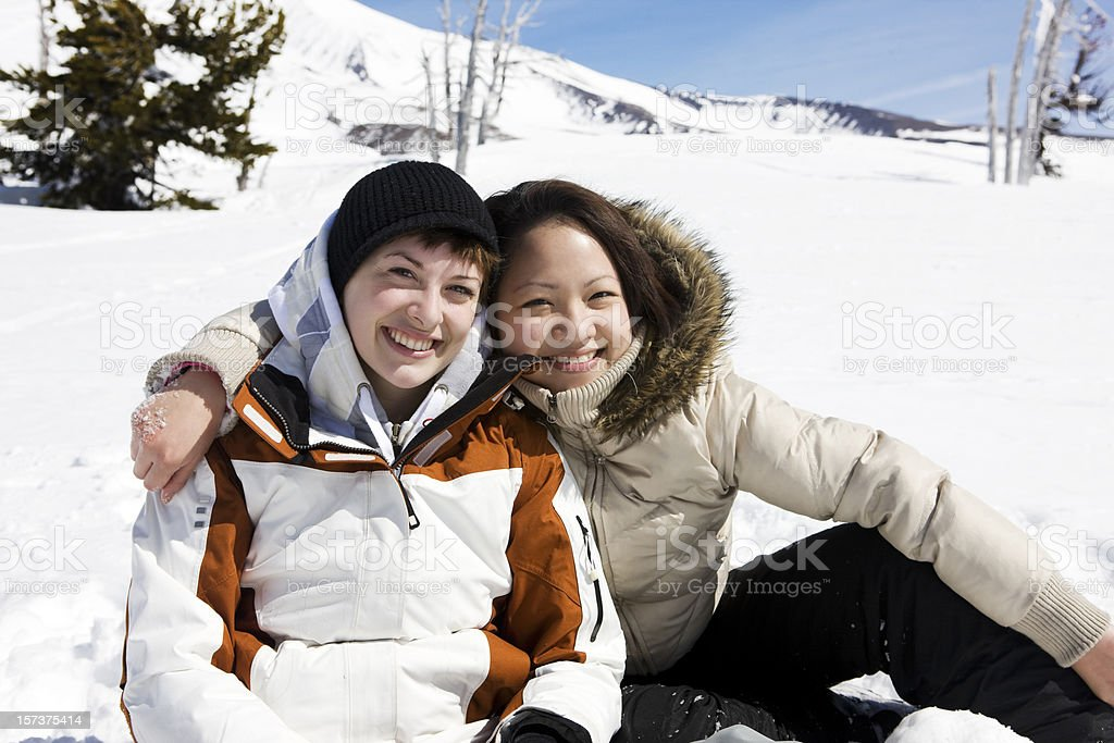 Asian and Caucasian Young Women Friends on Mountain Snow, Portrait royalty-free stock photo