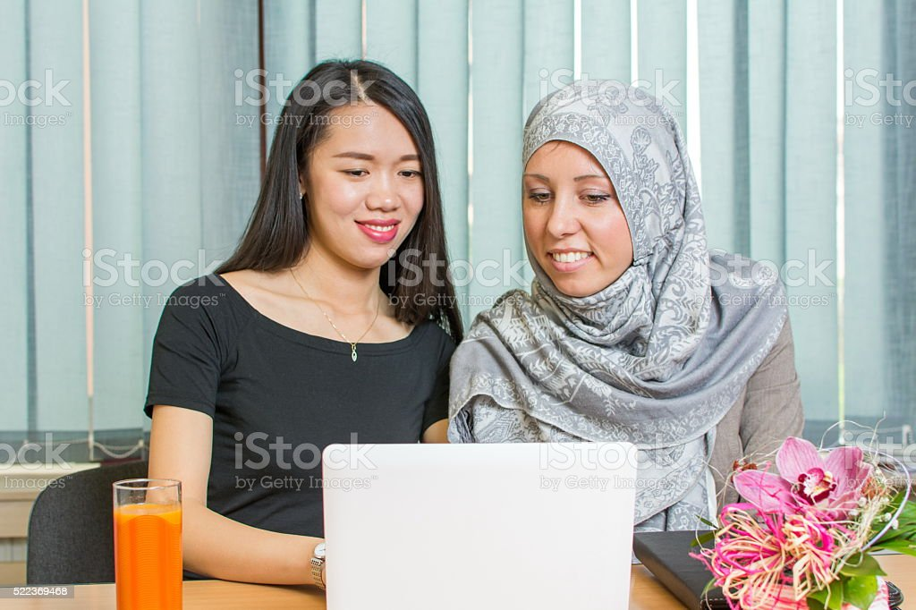 Asian and muslim girls working on a laptop stock photo