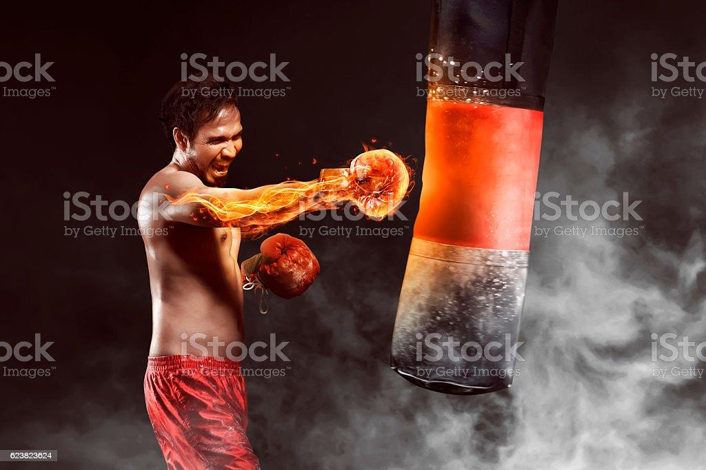 Asian athlete boxer punching a punching bag stock photo
