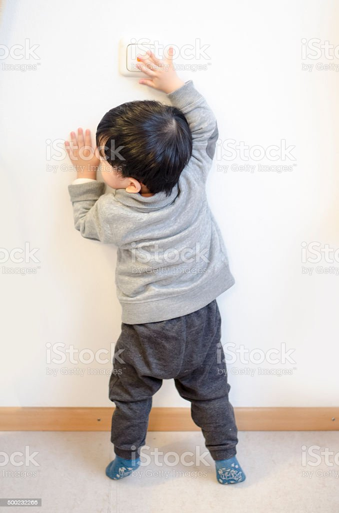 Asian Baby Boy playing the light switch stock photo