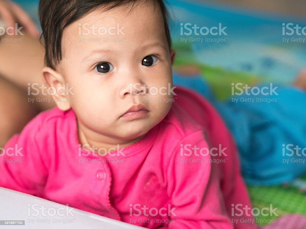 Asian baby crawling on the floor and looking straight. royalty-free stock photo