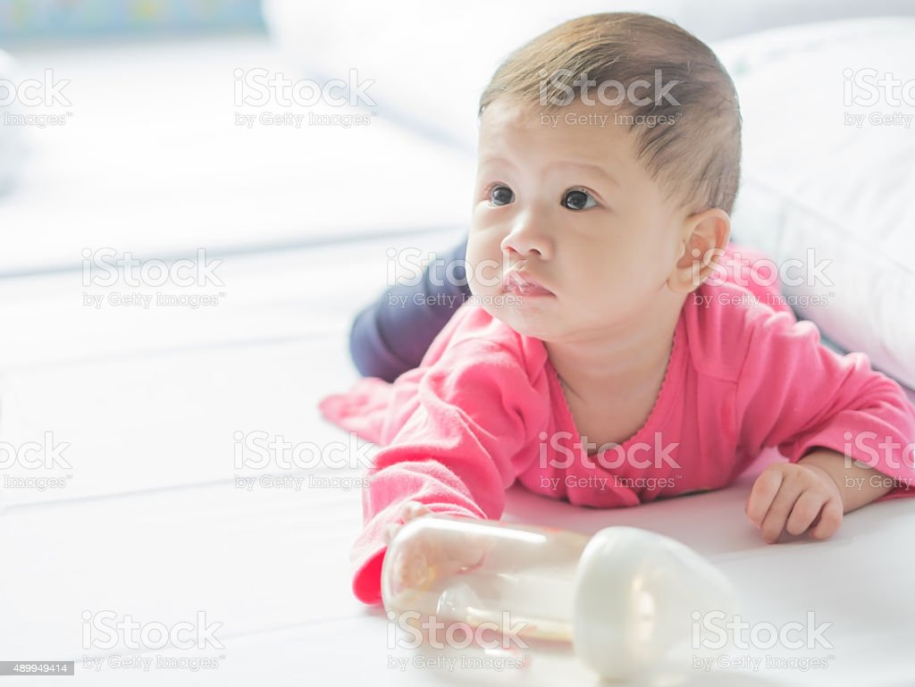 Asian baby girl crawling on the bed with messy mouth. royalty-free stock photo