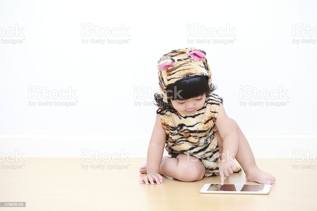 Asian baby girl in tiger suit with electronic tablet royalty-free stock photo