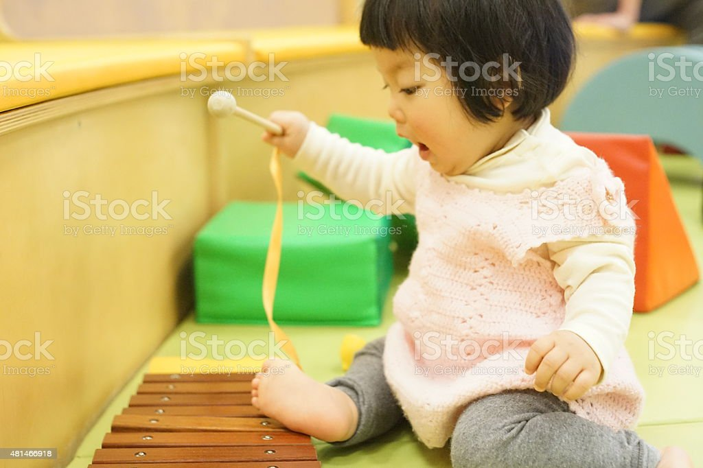 Asian baby girl playing the xylophone stock photo